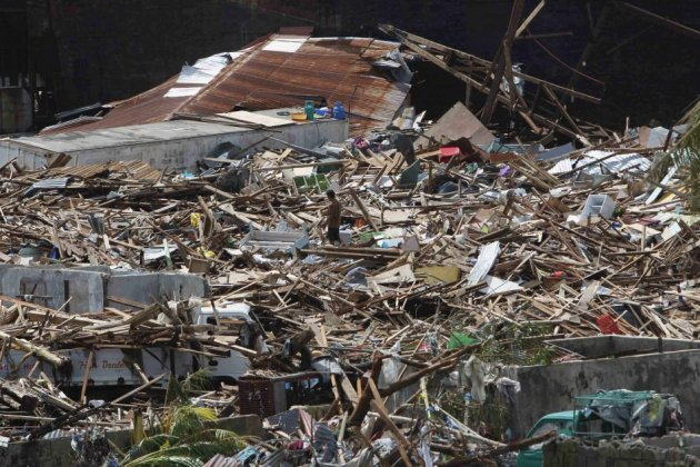 A survivor walks on debris of houses destroyed by Haiyan