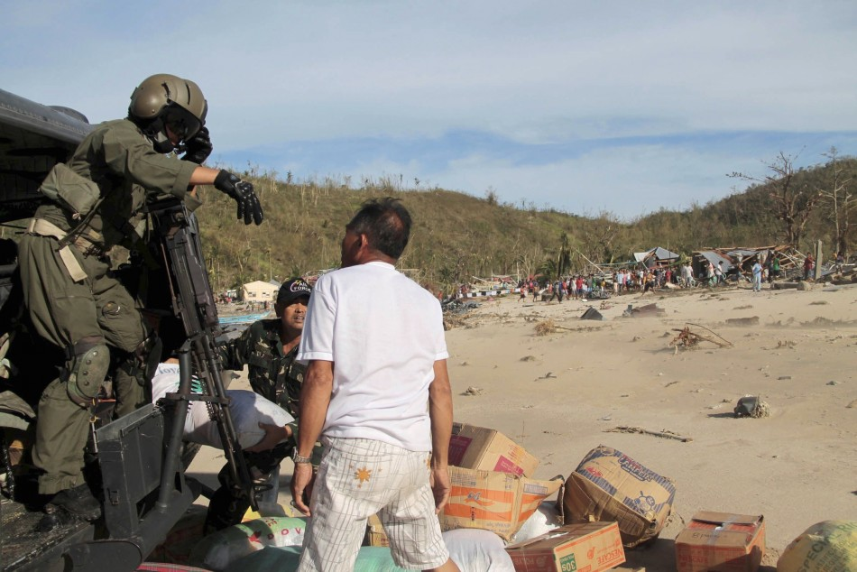 Members of Tactical Operations Group of Philippine Air Force unload relief goods to isolated residents after Typhoon Haiyan hit village in Panay island