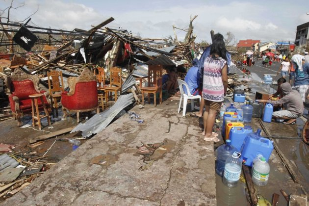 Survivors queue to get water from faucet near damaged houses
