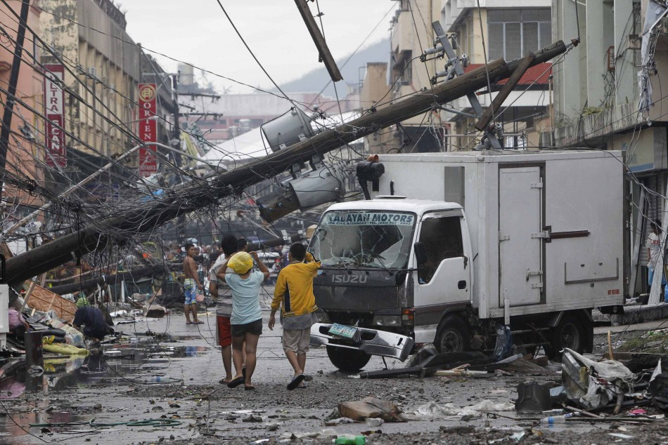 Survivors walk under a fallen electric post in battered Tacloban city