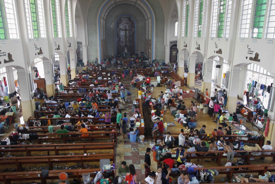 People take refuge in a Catholic church converted to a disaster relief centre in Tacloban City.