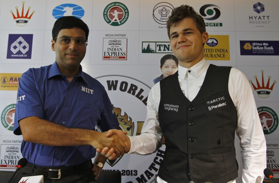 India's Viswanathan Anand (L) shakes hands with Norway's Magnus Carlsen during their joint news conference ahead of the FIDE World Chess Championship in the southern Indian city of Chennai November 7, 2013.