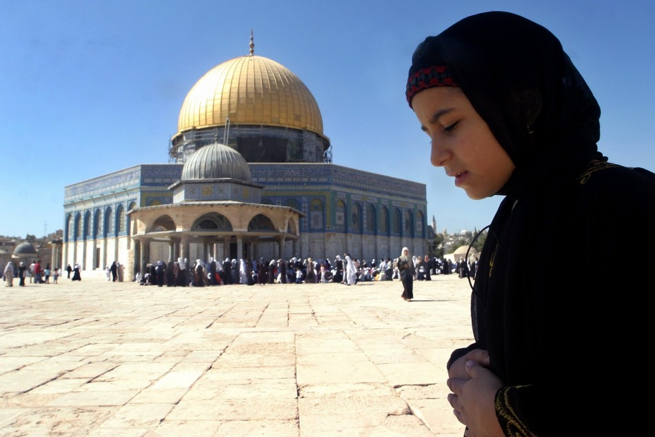 Palestinian girl prays during holy month of Ramadan in front of the Dome of the Rock mosque in Al-Aqsa mosque compound