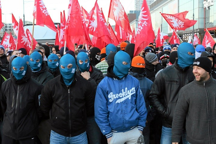 Far-right protesters march with faces covered during their annual march (Reuters)