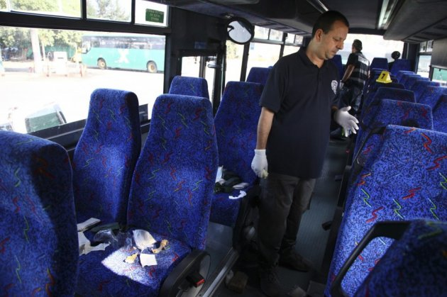 An Israeli policeman surveys the scene of a stabbing incident on a bus in the northern Israeli town of Afula
