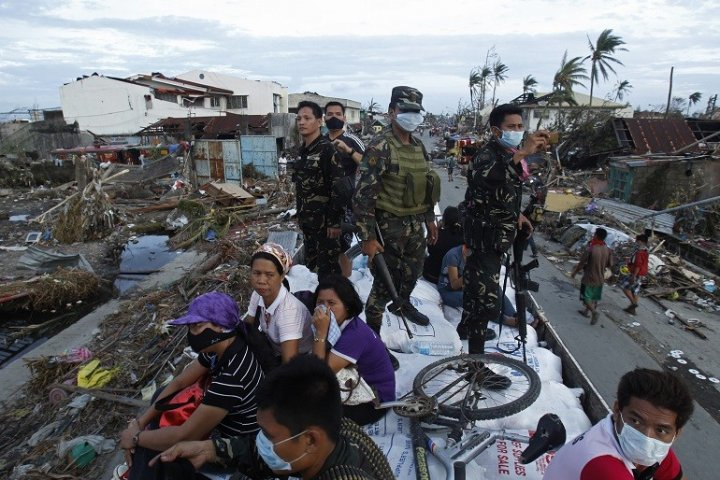 Soldiers and survivors of Typhoon Haiyan survey damage in Talcoban PIC: Reuters