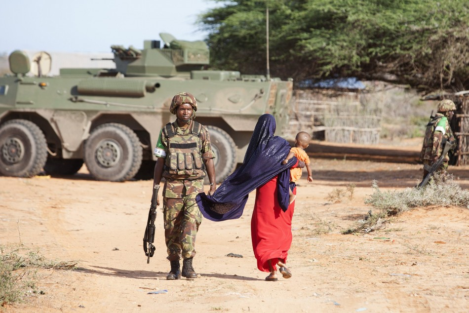 A woman walks by a Kenya Defence Force (KDF) soldier on the outer perimeter area of the Kismayu airport controlled by the African Mission in Somalia (AMISOM)