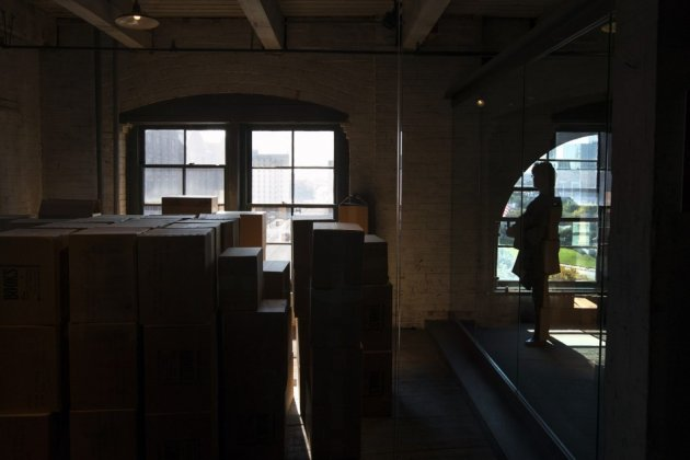 A woman looks toward an enclosed area on the sixth floor of The Sixth Floor Museum at Dealey Plaza