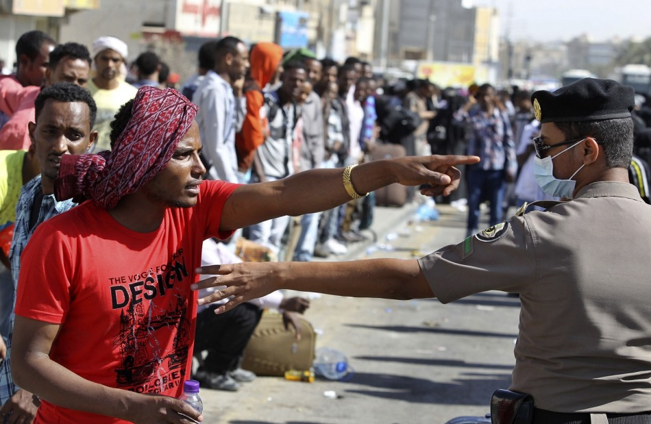 An Ethiopian worker argues with a member of the Saudi security forces as he waits with his countrymen to be repatriated in Manfouha, southern Riyadh