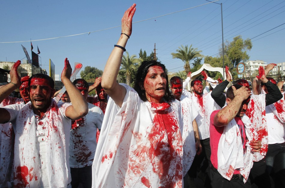 A Shi'ite Muslim woman marches with men, who are bleeding after tapping their foreheads with razors, during a Muharram procession. (Photo: REUTERS/Ali Hashisho)