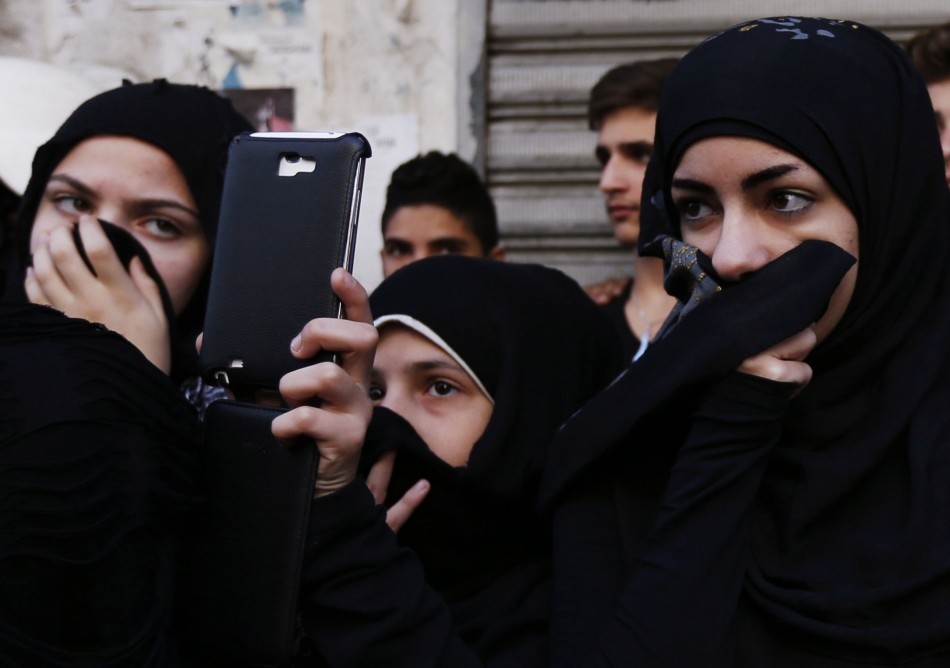 Lebanese women cover their noses as a girl next to them takes pictures of a Muharram procession to mark Ashura in Beirut. (Photo: REUTERS/Jamal Saidi)