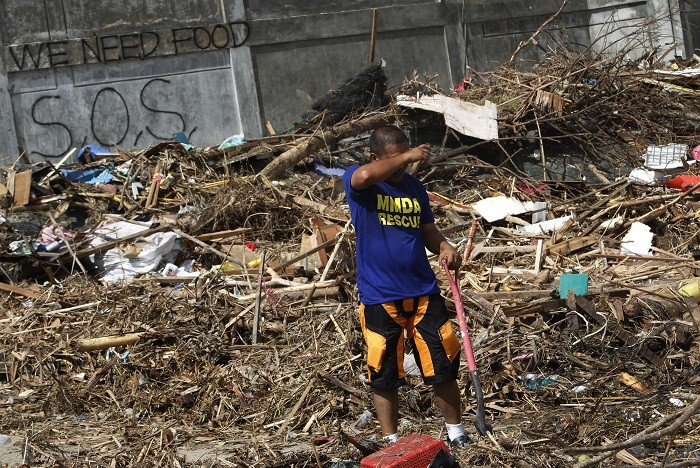 Rescue worker searches for missing typhoon victims, which include 61-year-old Colin Bembridge and his young family.