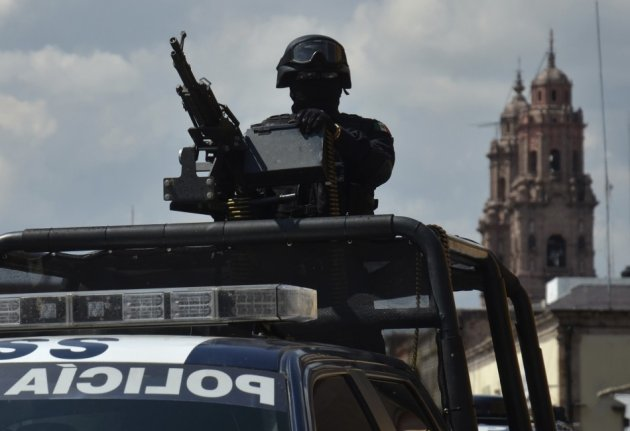 Federal police officers patrol the streets of Morelia, Michoacan.