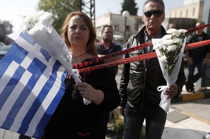 Mourners stand outside Golden Dawn's Athens office, where two members of the far-right group were shot in November. (Reuters)