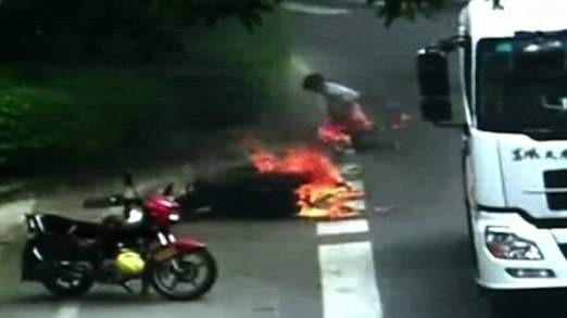 The motorcyclist catches fire after the accident in Foshan City, China.