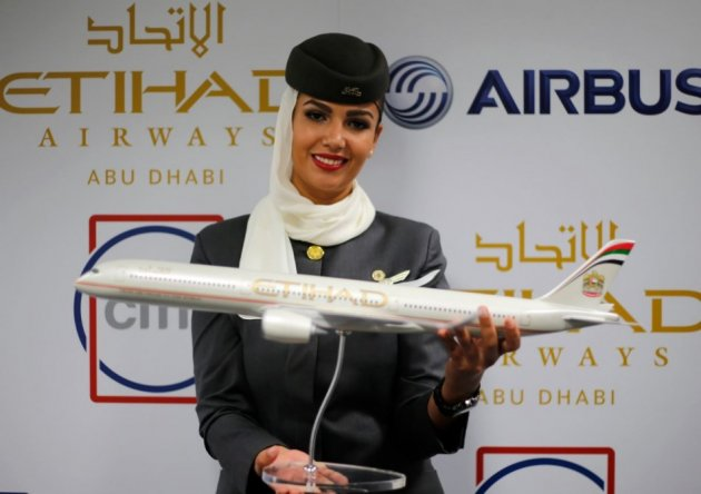 A flight attendant of Etihad Airways holds a model of the Airbus A350 during the Dubai Airshow. (Reuters)