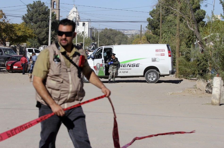 A forensic technician cordons off a crime scene in Ciudad Juarez