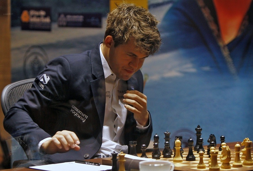 Carlsen reaches ponders his move against Viswanathan Anand during the FIDE World Chess Championship