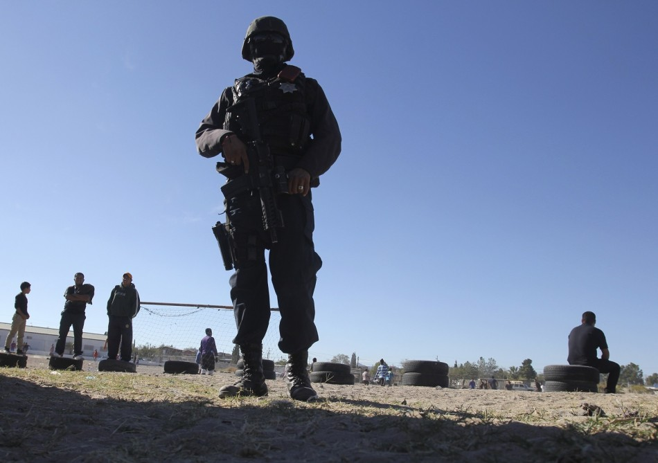 A police officer guards the perimeter of a house where a family was killed as neighbours play football in Ciudad Juarez