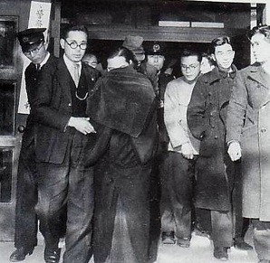Miyuki Ishikawa surrounded by police officers