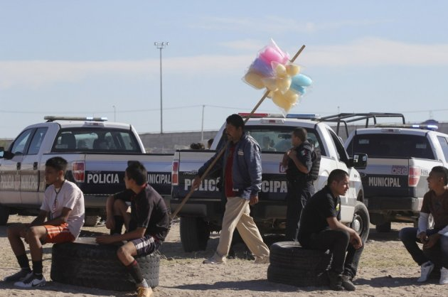 A man selling candy floss walks past patrol cars as a police officer guards the perimeter of a house where a family was killed in Ciudad Juarez