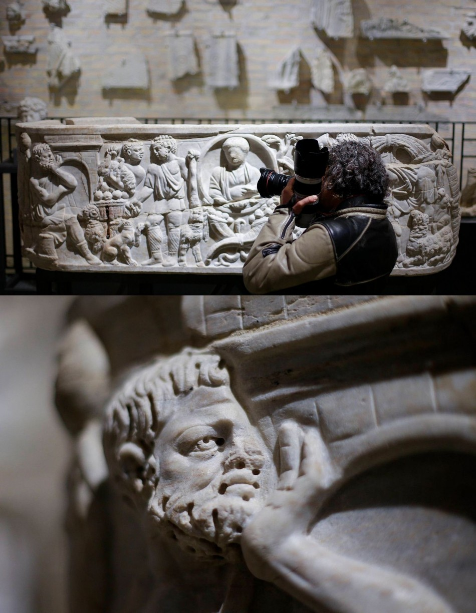 A photographer takes pictures of a marble low-relief decorating a sarcophagus inside the catacomb of Priscilla. (Photo: REUTERS/Max Rossi)