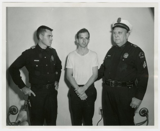 ee Harvey Oswald, accused of assassinating former U.S. President John F. Kennedy, is pictured with Dallas police Sgt. Warren (R) and a fellow officer in Dallas