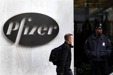 A man walks past the Pfizer logo next to a New York Police Officer standing outside Pfizer's world headquarters in New York.