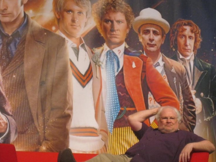 Colin Baker sits in front of a picture of him as The Doctor for the Doctor Who 50th Anniversary celebration (Photo: Lianna Brinded, IBTimes UK)
