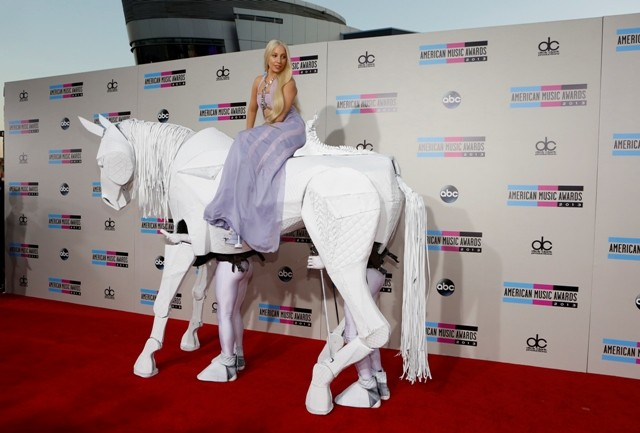 Musician Lady Gaga arrives atop a horse puppet