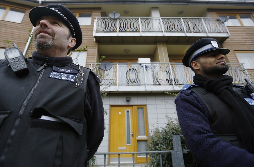 Police stand guard at a property in Brixton, south London where the three women escaped (Reuters)