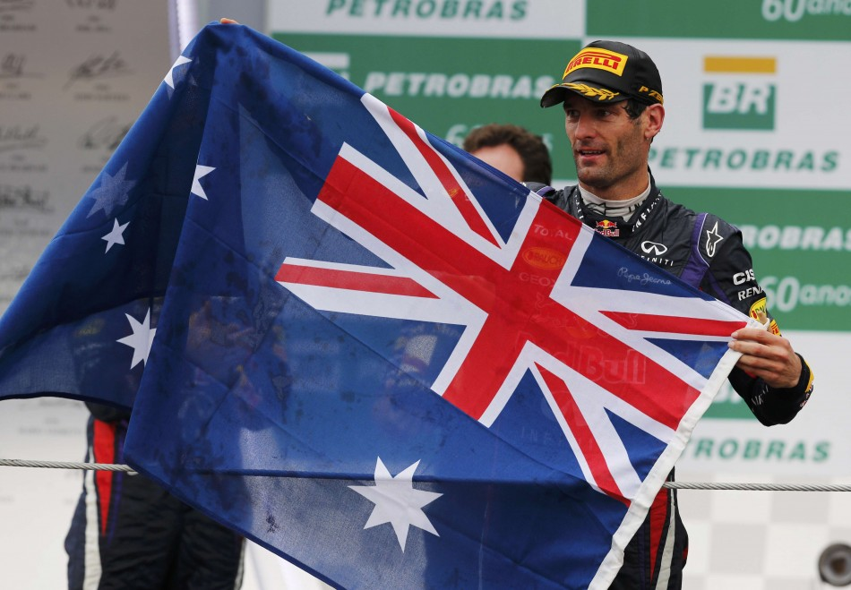 Red Bull Formula One driver Mark Webber of Australia holds up the Australian flag during podium celebrations after the Brazilian F1 Grand Prix at the Interlagos circuit in Sao Paulo November 24, 2013. REUTERS/Paulo Whitaker