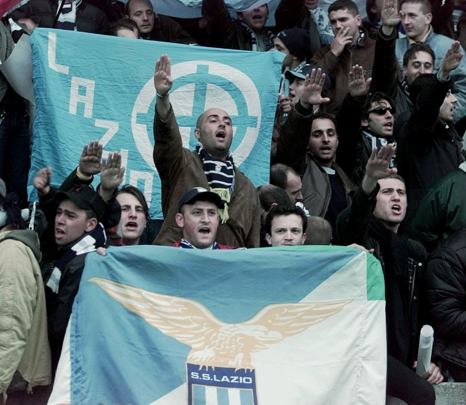 Fans for Italian team Lazio give the Nazi salute as they hold team banners
