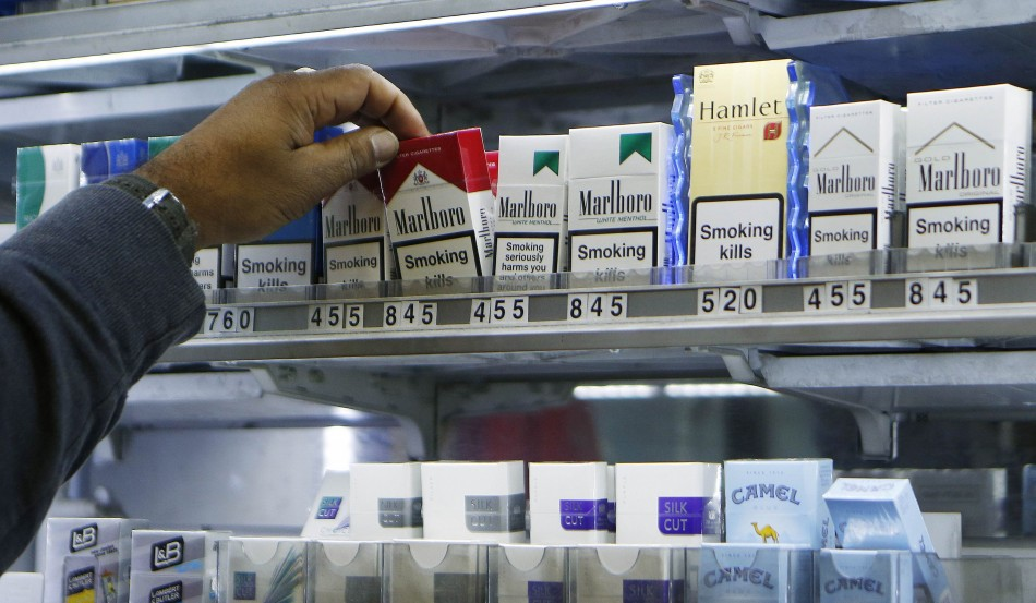 A shopkeeper reaches for a packet of cigarettes in a newsagent in London November 28, 2013. Britain announced an independent review of tobacco packaging on Thursday and said it was ready to introduce new laws banning branding on cigarette packets if the r