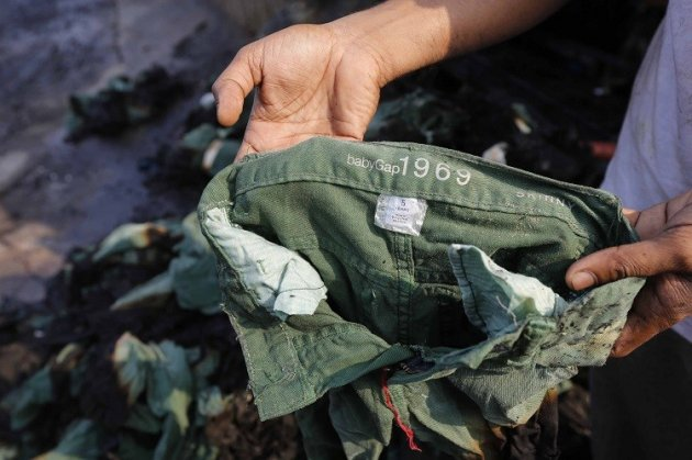 An employee shows the brand of a burnt clothing item in front of a Standard Group garment factory which was on fire in Gazipur November 29, 2013. (Photo: Reuters)