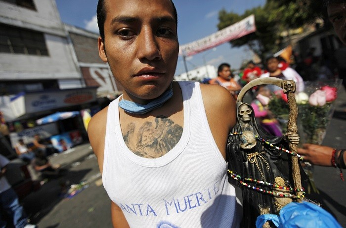 Santa Muerte follower holds a figure of the 'saint', which is blamed for a rise in exorcisms and drug-related violence in Mexico. (Reuters)