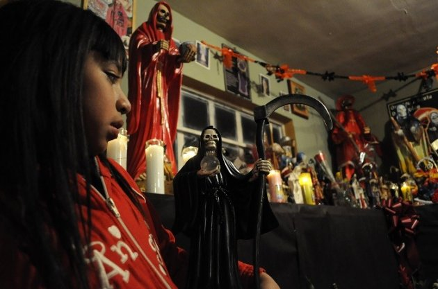 A girl pays homage to Santa Muerte in a shrine in Mexico. (Reuters)