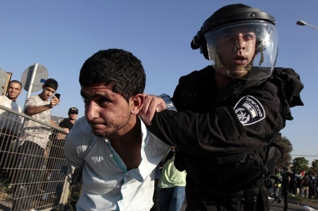 An Israeli policeman detains a protester during a demonstration in solidarity with Palestinian Bedouins. (Reuters)