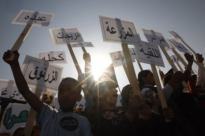 Israeli Arab children hold placards, some of which name Bedouin villages not recognised by Israel. (Reuters)