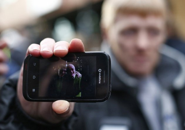 John McGarrigle shows reporters a photo of him and his father John McGarrigle senior, sitting in their favourite spot at the Clutha pub, the site of a helicopter crash in the centre of Glasgow. (Reuters picture)