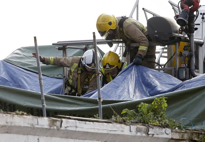 Members of the emergency services use a cherry picker to access the crash site of a police helicopter on the roof of a pub in the centre of Glasgow (Reuters picture)