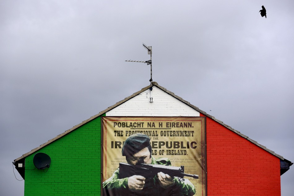 A crow flies past a mural in the Ardoyne area of North Belfast displaying an image of a I.R.A. gunman November 5, 2013
