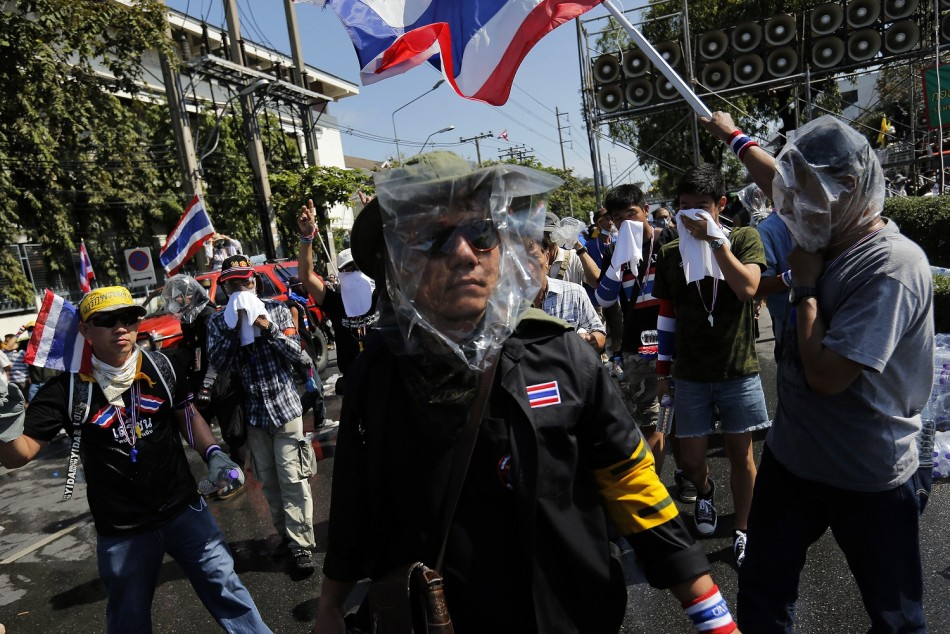 Masked anti-government protesters get ready to attack a barricade during clashes with police near the Government house in Bangkok