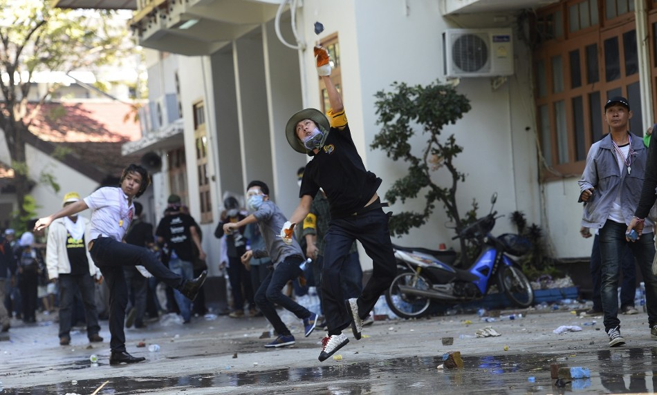 Anti-government protesters throw rocks at Thai Riot police as they attack Government House in Bangkok