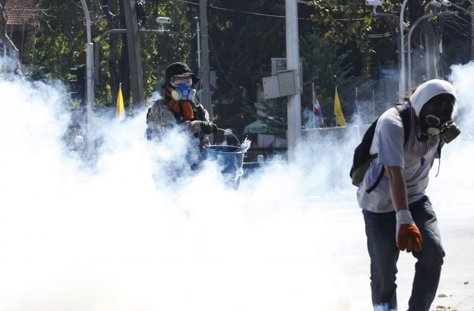Anti-government protesters try to retrieve a teargas canister during clashes with police near the Government House in Bangkok
