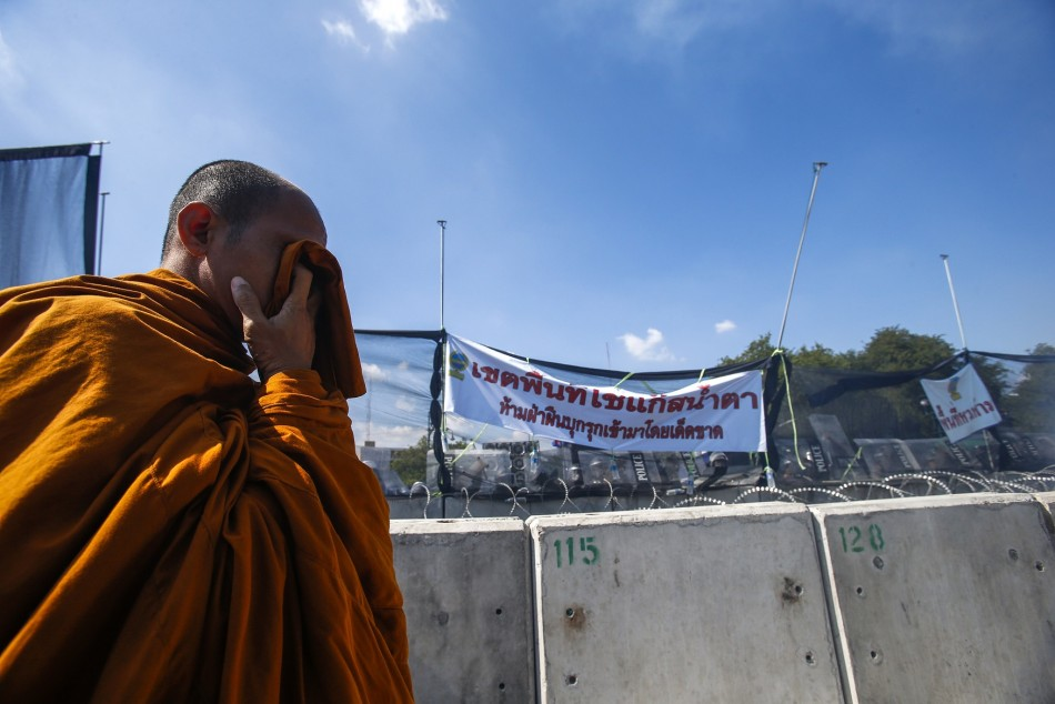 A Buddhist monk covers his face with wet handkerchief during clashes with police near government house in Bangkok