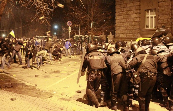 Protesters throw stones at police during a rally held by supporters of EU integration in Kiev December