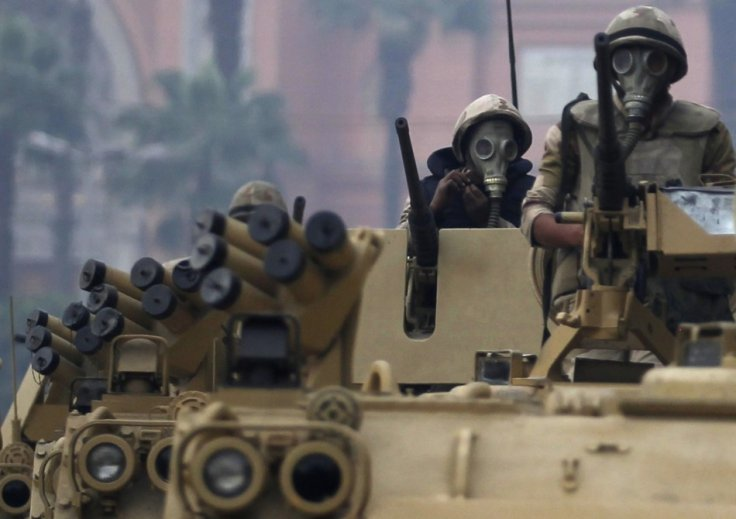 Soldiers riding armoured personnel carriers (APC) arrive at Tahrir Square after clashes with pro-Mursi protesters in Cairo