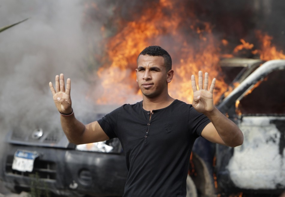 A pro-Mursi university student and supporter of the Muslim Brotherhood gestures with four fingers in front of a burning police vehicle at Al Nahda square in Cairo