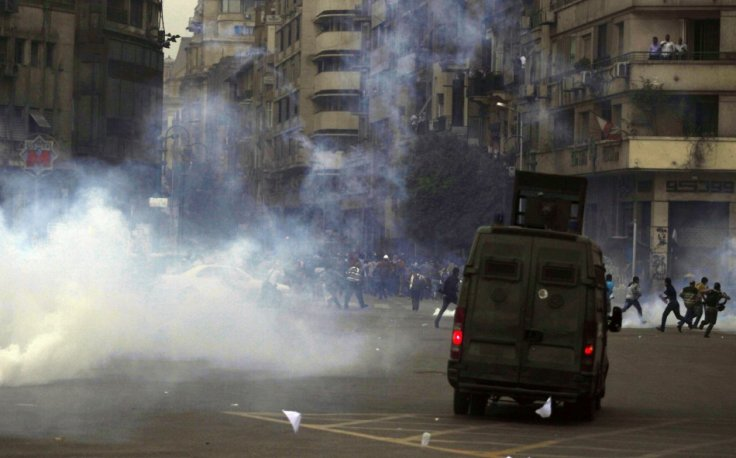 Supporters of the Muslim Brotherhood and ousted Egyptian President Mohamed Mursi flee teargas fired by riot police at Tahrir Square in Cairo